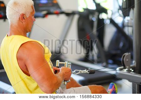 Middle-aged instructor does exercises on simulator in modern gym