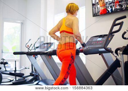 Middle-aged woman in orange runs on treadmill in modern gym, и�?�Ð» м�?�?�?