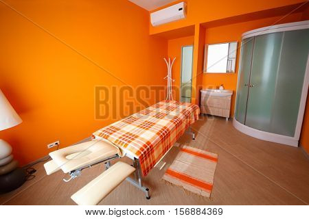 Empty room with table for massage, aromatherapy, relaxation and shower cabin