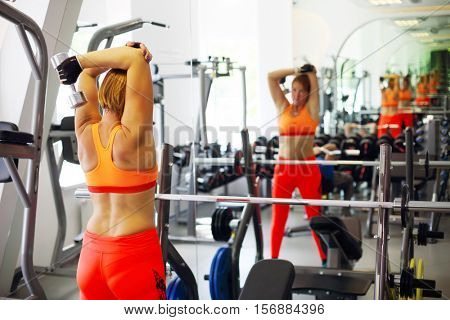 Middle-aged woman in orange does exercises with dumbbells in modern gym with simulators