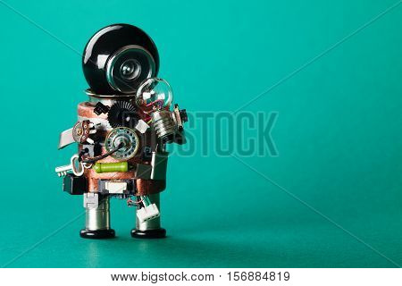 Creative idea concept with robot looking at light bulb. retro style toy character with funny black helmet head. Copy space green background