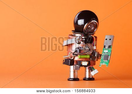 Robot with usb flash storage stick. Data storing and robotic technology concept fun toy character black helmet head. Copy space orange background macro view