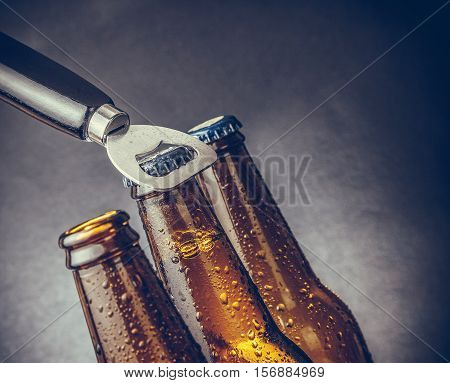 Three Fresh Cold Beer Ale Bottles With Drops And Stopper Open With Bottle Opener