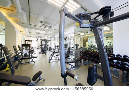Modern gym with new shiny fitness equipment, big mirror for sport training