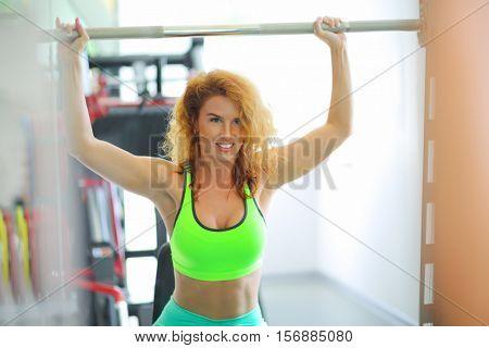 Happy beautiful woman raises barbell in modern gym, shallow dof