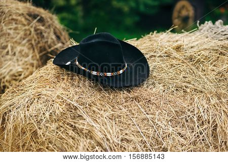 Black cowboy hat lay on the bale of hay. Decorated with ornaments made by hand.