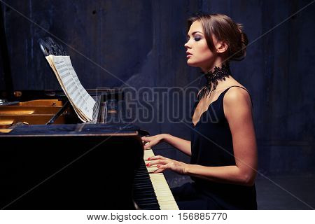 Mid side view of contented carefree female enjoys the opportunity of performing on the piano while sitting in studio