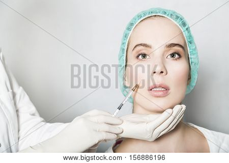 Doctor aesthetician makes hyaluronic acid beauty injections in the nasolabial fold of female patient in a green medical cap poster