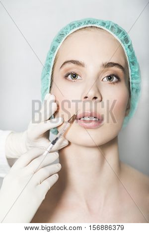 Doctor aesthetician makes hyaluronic acid beauty injections in the nasolabial fold of female patient in a green medical cap