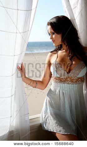 Beautiful brunette lingerie model at a beach house window