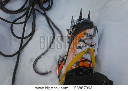 Ice climbing shoes in the snow with rope