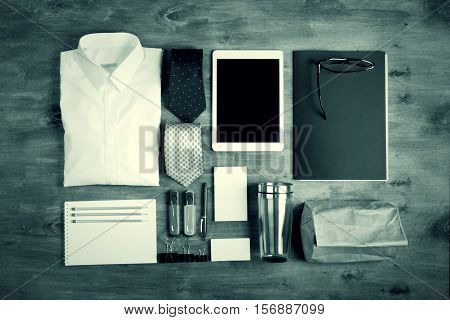 Business objects on the desk, including digital tablet, shirt, ties, lunch box, paper and pencils, top view, monochrome