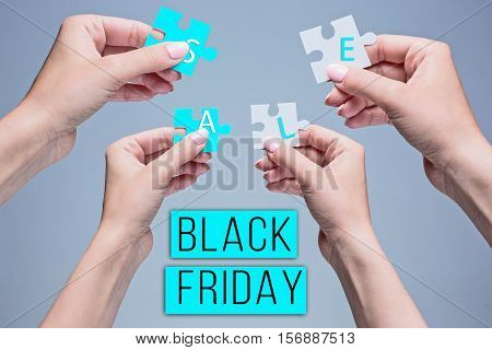 The puzzles in hands on gray background. Black Friday sale - holiday shopping concept