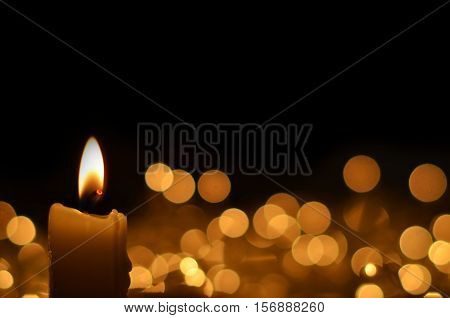 On a black background burning candle. on the background of blurred lights garlands. Space for text