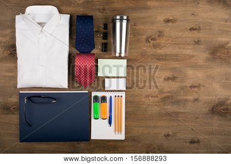 Business objects on the desk, including digital tablet, shirt, ties, lunch box, paper and pencils, top view with copy space