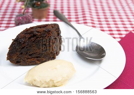 Christmas pudding A traditional British Christmas steamed pudding decorate with holly served with brandy sauce