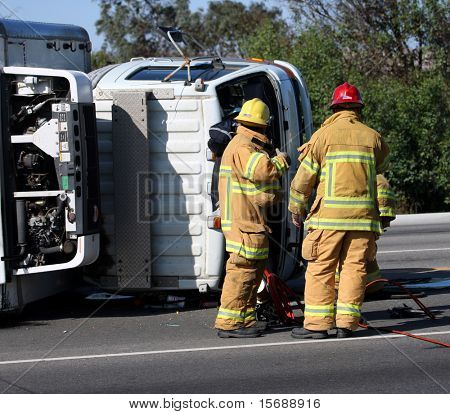 Firefighters at the scene of a turned truck