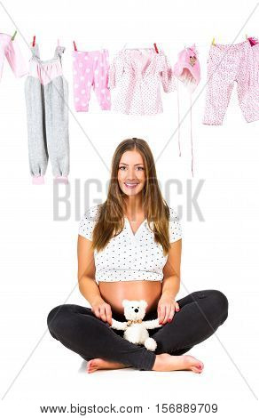 Pregnant young woman and baby clothes, isolated on white