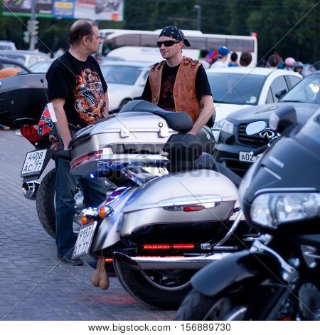 MOSCOW RUSSIA - OCTOBER 6 2013: Biker in a bandana wearing sunglasses and leather vest talking with a balding man in a black T-shirt with a dragon. Motorcycles stand in a row on the viewing platform Vorobyovy Gory near Moscow State University named after