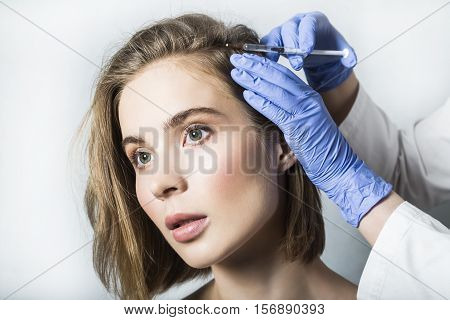 Doctor aesthetician in blue medical gloves makes hyaluronic acid rejuvenation beauty injections in the back of the head of beautiful young female patient for hair growth and to prevent boldness.