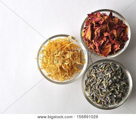 Dried marigold (calendula) petals with lavender and rose for beauty treatments in clear glass bowls -top view with copy space