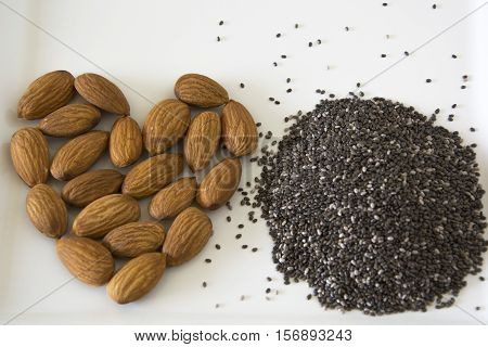 Almonds in a heart shape along with a pile of chia seeds