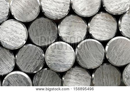 Background texture and pattern of aluminium bars with focus to the cut and bevelled ends of the round metallic silver rods in a full frame view