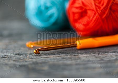 Close up of different crochet hooks on a wooden table