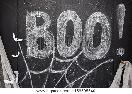 Word Boo drawn with white crayon on black drawing board decorated with paper handmade bats and web. Decor of photobooth for Halloween party. Vertical color photo.