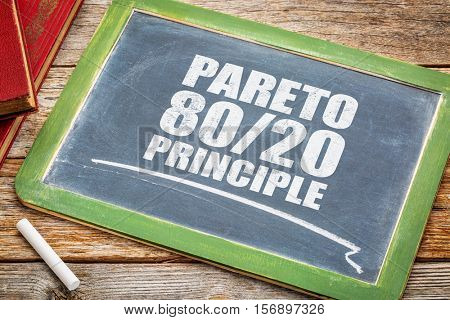 Pareto principle or eighty-twenty rule - white chalk text on a vintage blackboard blackboard with books