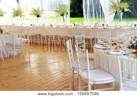 Bright airy event venue or salon with formal decorated tables with stylish white linen and a view onto a garden past vases of fresh flowers