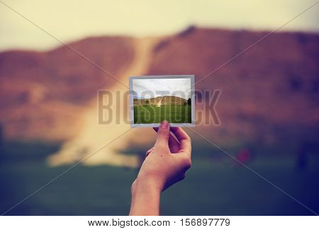 a young girl holding an instant photo in front of a landscape that is the same but a close up instead of a wide angle toned with a retro vintage instagram filter app or action effect