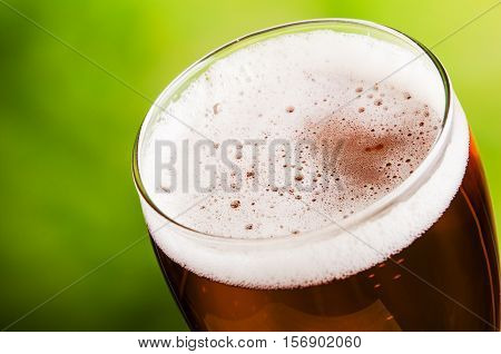 Glass of beer on a green background