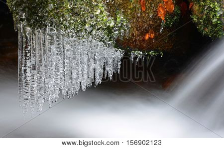Winter creek with icicles in the national park Sumava,Czech Republic.