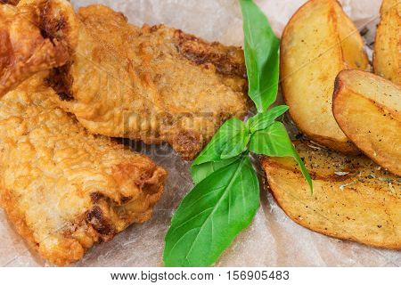 Fried fish in batter with potatoes and tartar sauce served on paper closeup