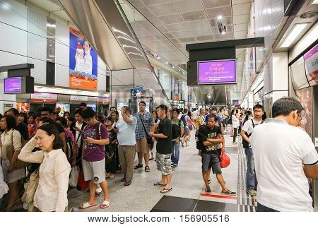 Singapore - November 16, 2012. A crowd of people in Singapore subway waiting for the train.