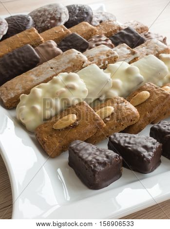Closeup of an assortment of typical German Gingerbreads such as Lebkuchen Aachener Printen and Spitzkuchen arranged on a large white porcelain serving plate. Selective Focus. Shallow Depth of Field.