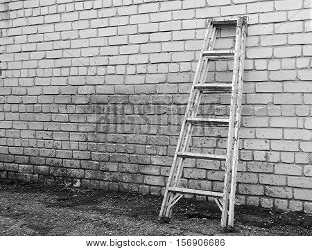 Old ladder staircase against a brick wall