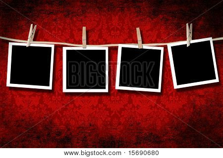 Blank photographs hanging with grungy velvet background