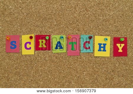 Scratchy word written on colorful sticky notes pinned on cork board.