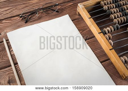 Vintage abacus envelopes on wooden table, concept of traditional business