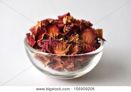 Dried rose petals in a clear glass bowl for beauty treatments and cosmetic products