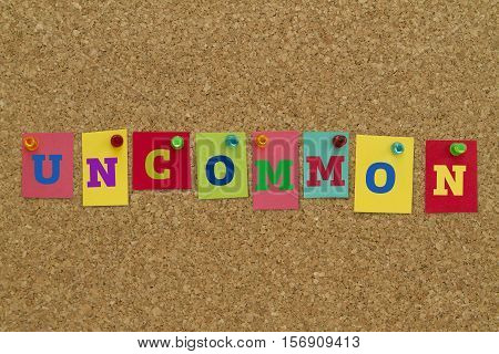 Uncommon word written on colorful sticky notes pinned on cork board.