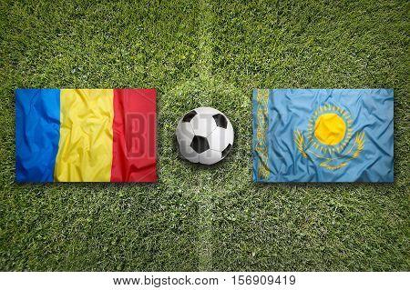 Romania vs. Kazakhstan flags on a green soccer field, 3D rendering