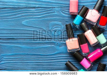 lot of bottles of nail polish on dark wooden background top view