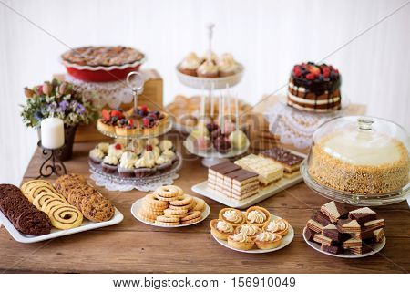 Brown wooden table with various cookies, tarts, cakes, cupcakes and cakepops. Studio shot.
