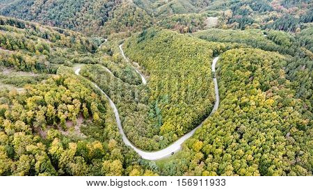 Aerial view of curvy road in the middle of green forest, low hills. Nova Bana, Slovakia. poster