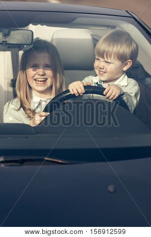 Couple of cute baby children friends of girl and boy people at wheel pretends driving car as drivers on road outdoor