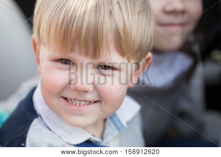 Cute baby boy kid or child portrait with blond hair with funny face outdoors