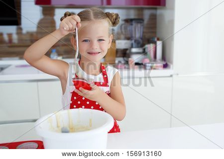 Little housewife blonde girl is 5 years old, his hair neatly gathered, dressed in a white vest and a red apron with white polka dots, prepares the dough for baking cakes in colorful forms, working on a large, bright kitchen